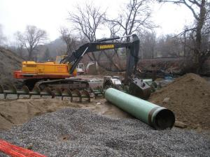 Heavy equipment next to large pipe on dirt created by digging on Main St.